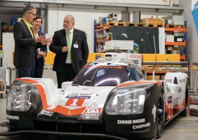 Dr. Peter Traut und Cornelia Grimm im Gespräch mit dem Unternehmensleiter neben einem Porsche Rennwagen