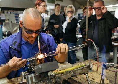Besucher der Industrie inTouch Thüringer Wald 2018 beobachten einen Mitarbeiter beim Bearbeiten von Glas