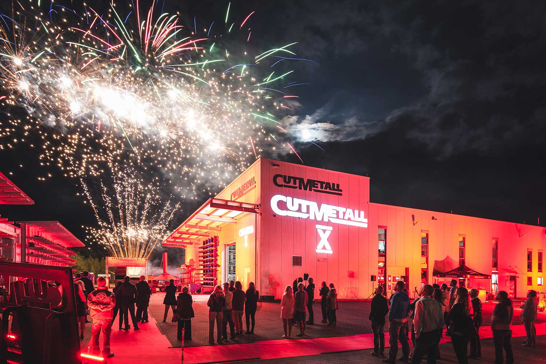 Firmengebäude von CUTMETALL Recycling Tools GmbH bei Nacht mit Feuerwerk