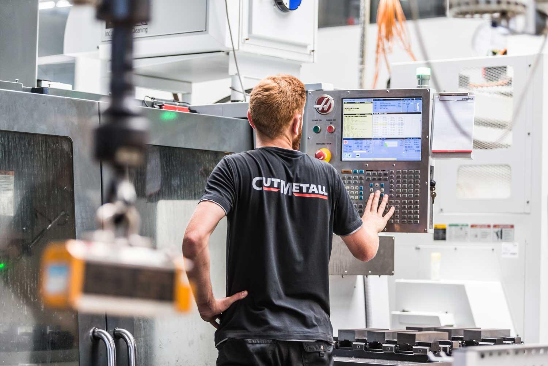 Mitarbeiter bei Cutmetall bei der Programmierung einer Produktionsmaschine
