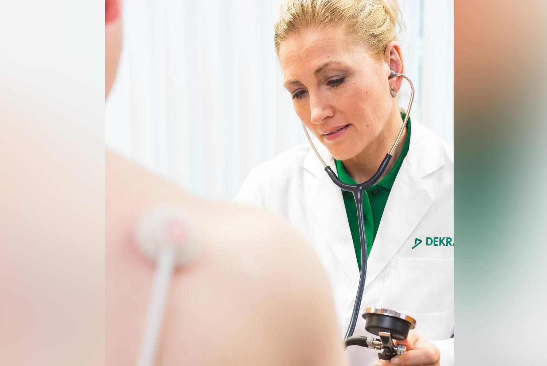 Medizinerin der DEKRA misst Blutdruck bei einer Person