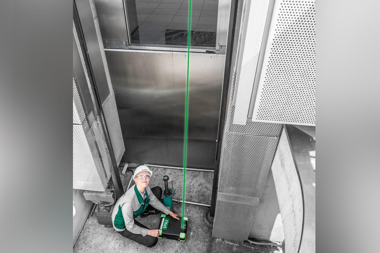 Mitarbeiterin der DEKRA positioniert Laser in einem Fahrzeugschacht