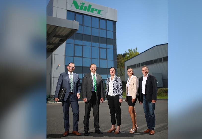 Personal der NIDEC GPM GmbH steht vor dem Firmengebäude