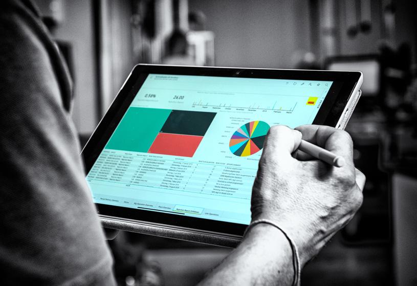 Ein Mitarbeiter von Sandvik Tooling Supply Schmalkalden arbeitet auf einem Tablet, auf dem verschiedene Diagramme zu sehen sind.