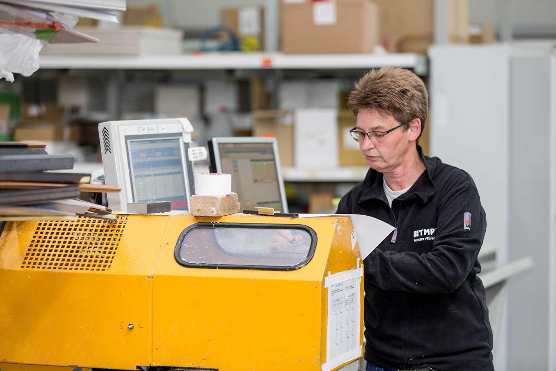 Mitarbeiterin an Maschine der TMP Fenster + Türen GmbH